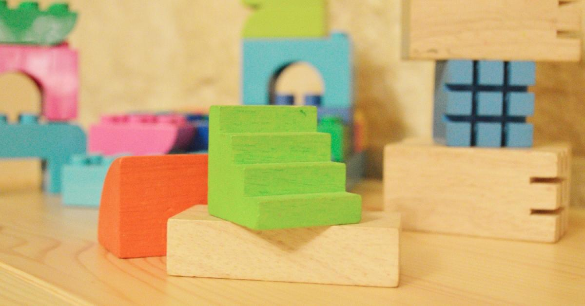 Green, orange, blue, pink and natural colored wooden blocks.