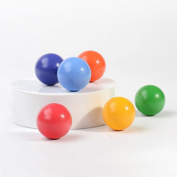 Colorful rainbow balls positioned on white platform.