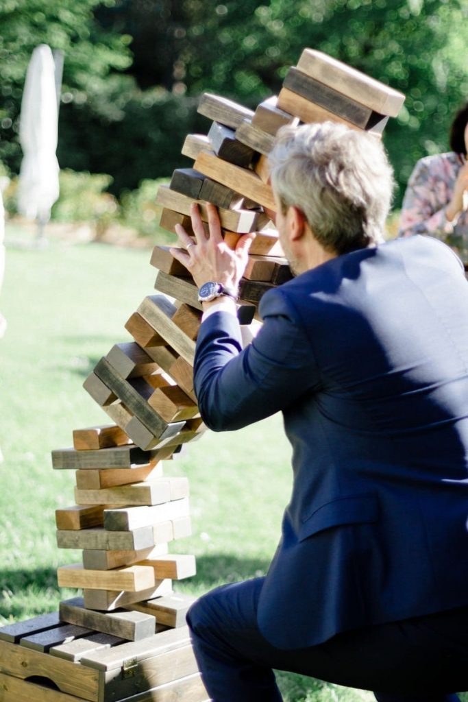 large wood jumbling tower toppled over by man in suit