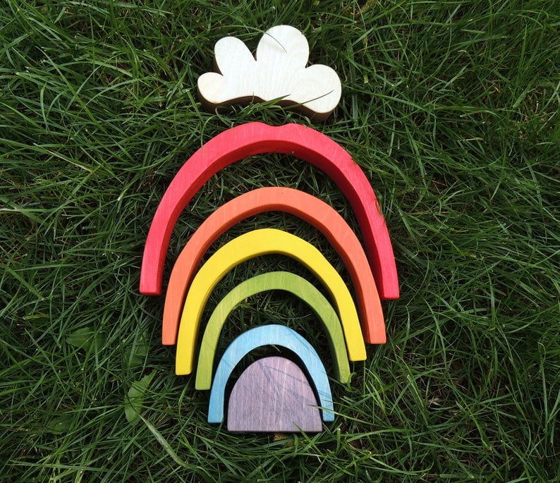 small wooden rainbow toy with cloud piece in grass