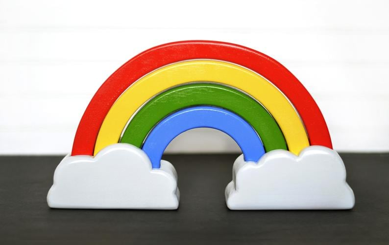 Wooden rainbow toy with cloud bases under both ends of the rainbow.