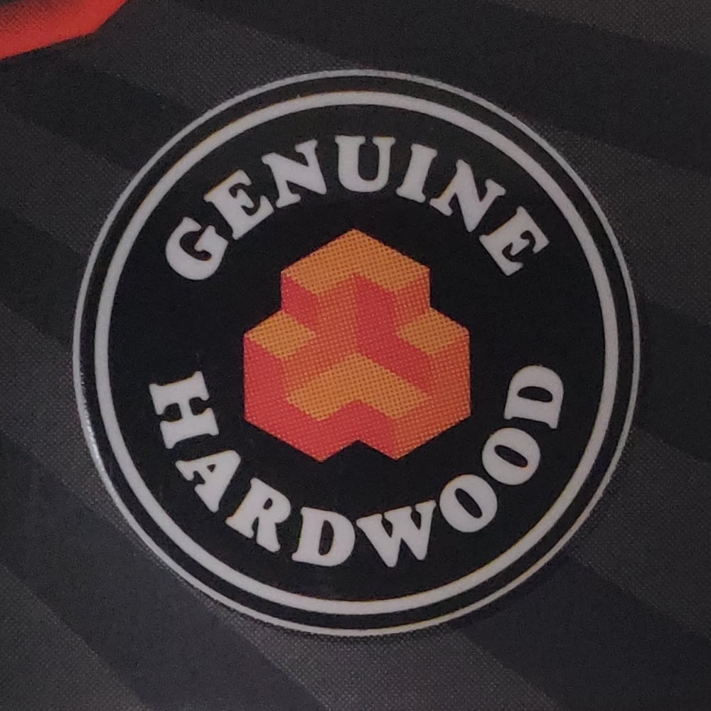 "Jenga Classic packaging badge design with words ""Genuine Hardwood""."