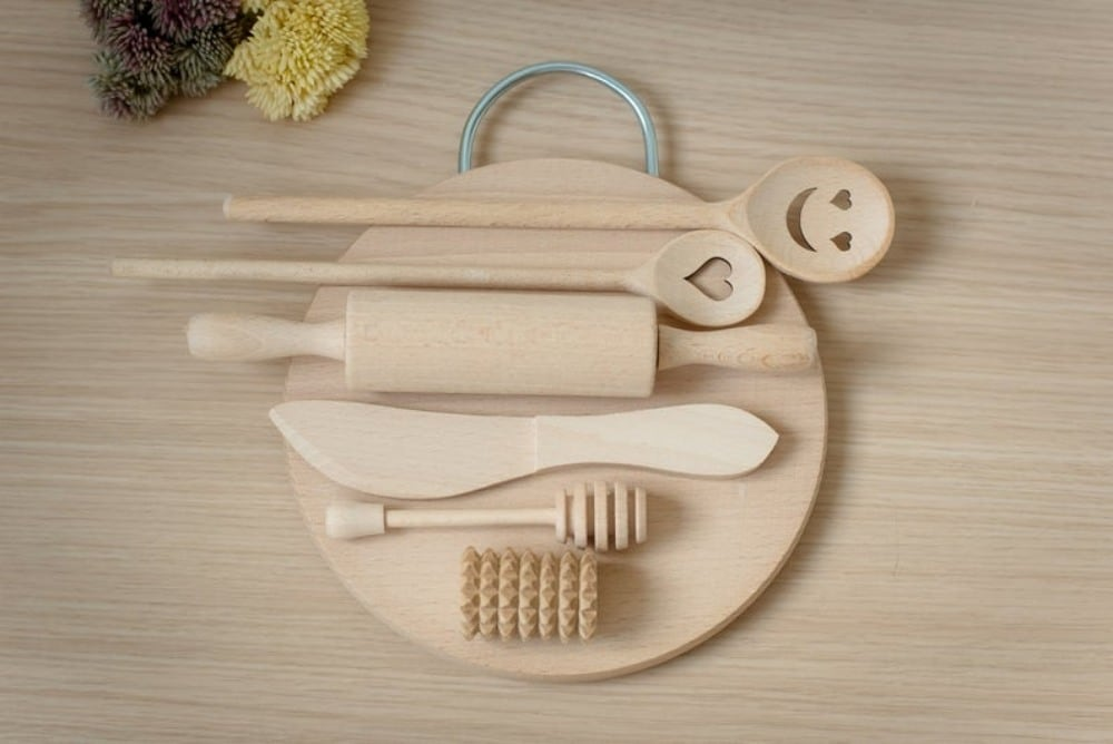 Montessorians brand wooden playdough toolset with circular cutting board.