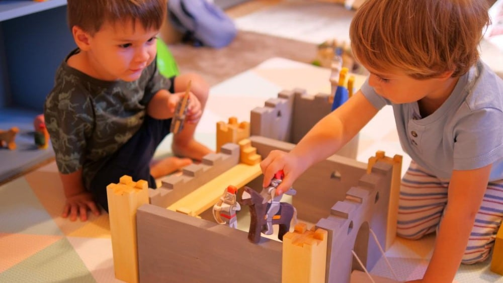 Two children playing with Vulps Toys brand handmade toy figurines andwooden castle.