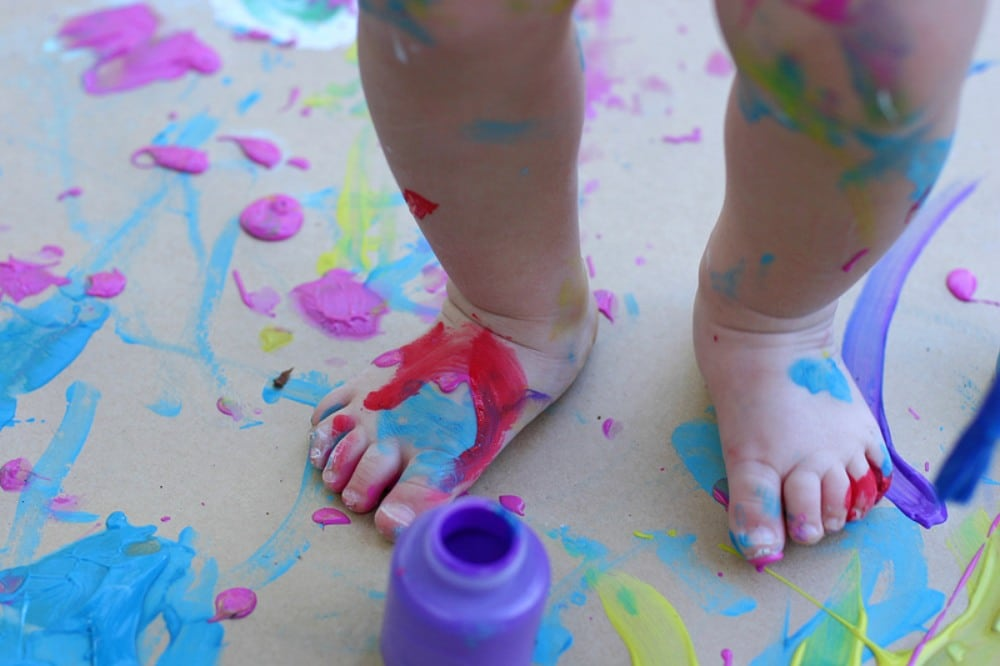 Finger Paint Smeared All Over The Floor And Young Toddlers Feet And Legs