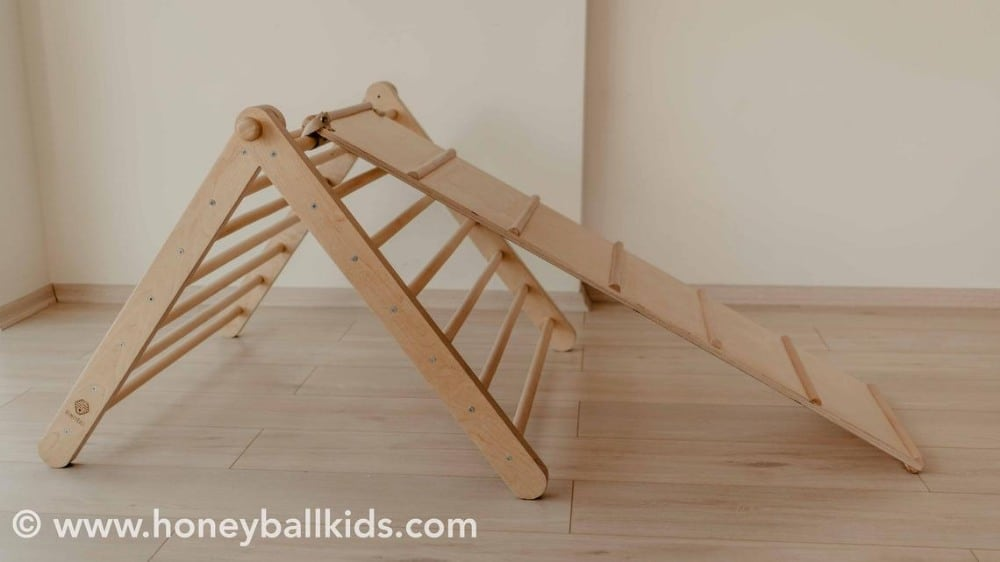 Honeyball kids adjustable wooden pikler triangle with reversible ramp for climbing.