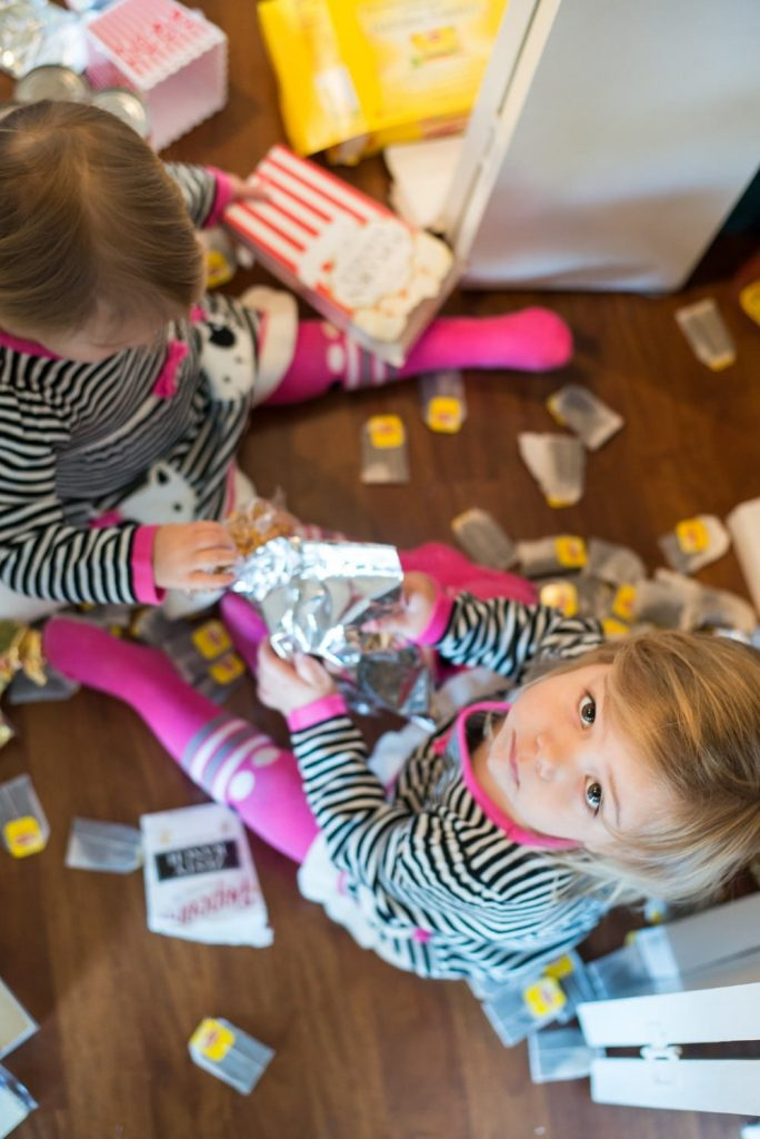 Two Toddler Girls Making A Mess With Tea Bags And Wrappers On The Kitchen Floor