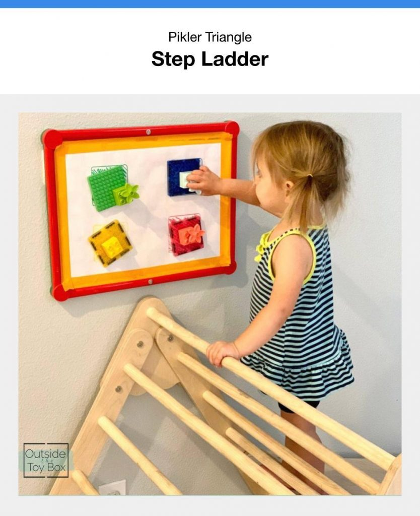 Toddler Using A Pikler Triangle As A Step Ladder To Reach A Wall Mounted Activity Board